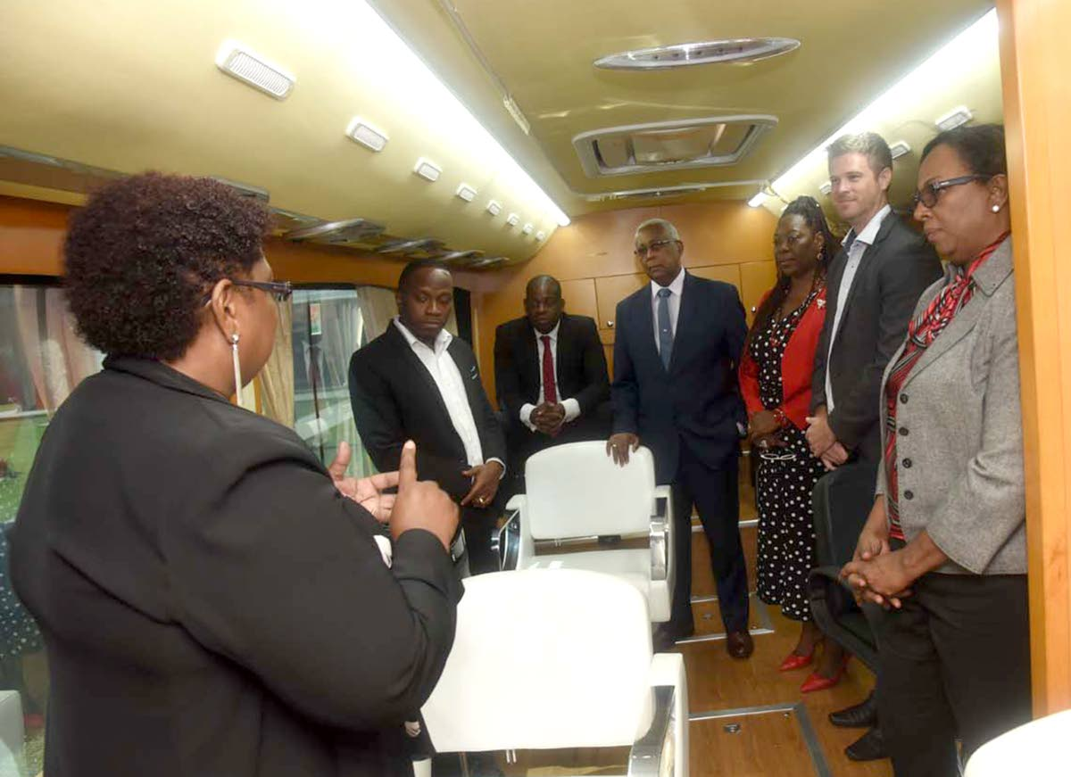 Donna Scoon-Moses, acting CEO, YTEPP, left, points out features of the mobile cosmetology training bus following the signing of a MOU between BPTT and YTEPP. From left are  Jesse Mose, deputy chairman, YTEPP; Minister in the Ministry of Education Dr Lovell Francis; Minister of Education Anthony Garcia; Dr Joan Spence, YTEPP Board member; William Blomfield, Acting Deputy High Commissioner, Australia; and Ronda Francis, corporate responsibility manager, BPTT.