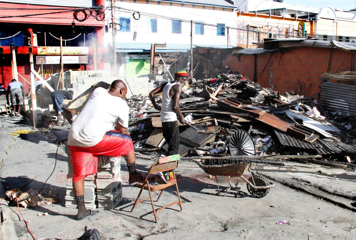 PUSHING AHEAD: Two owners of stores gutted by fire at the drag mall on Henry Street in Port of Spain work on removing debris from the area yesterday.   PHOTO BY SUREASH CHOLAI