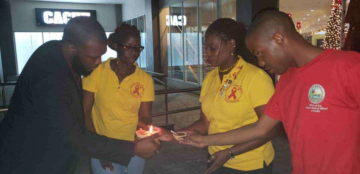 Minority Councillor and founder of the Imani Bet Knesset Foundation, Dr Faith BYisrael, second from right, lights deyas with supporters for a vigil to commemorate World Aids Day at the Gulf City mall, Lowlands on Friday.