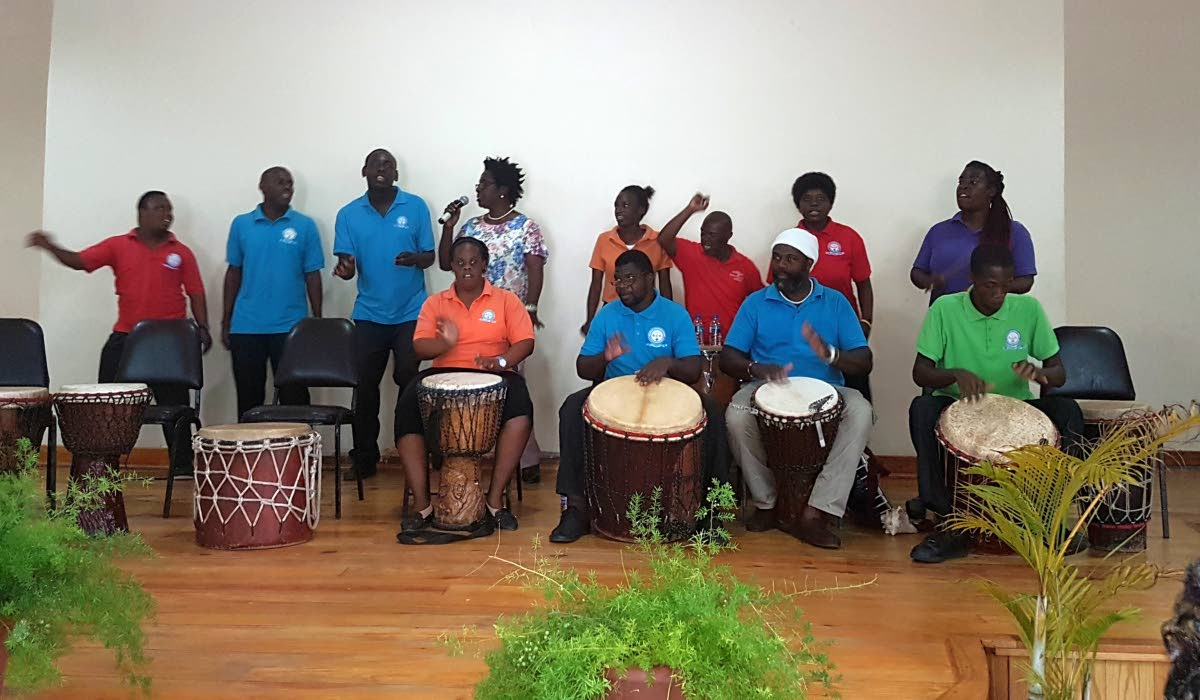 Students from TECVOC perform an item, accompanied by their teacher, Dotsie Bachus, back row, fourth from left, and drum instructor Courtney Potts, front row, second from right, at an observance of International Day of Persons with Disabilities.at the Canaan/ Bon Accord Community Centre on Monday.