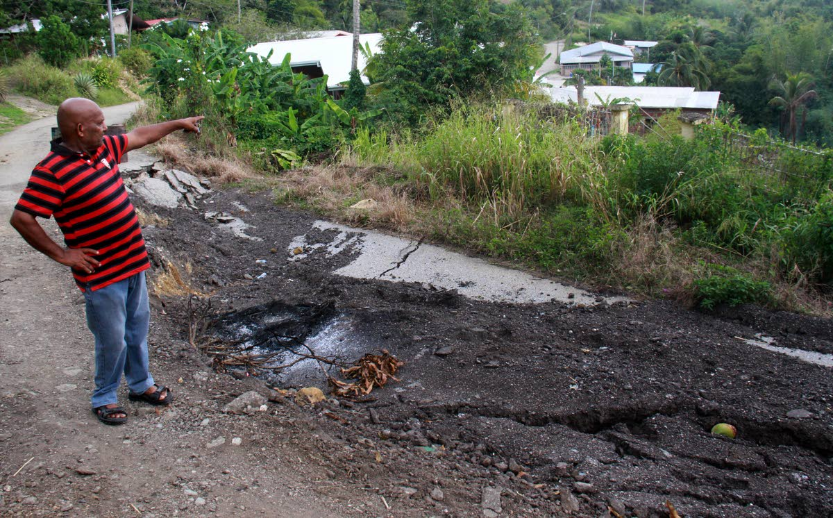 Basdeo Beharry, 68 points to some houses which is being affected by this major landslip where part of the  entire Mayo Road, Tortuga collapsed. PHOTO BY ANIL RAMPERSAD.