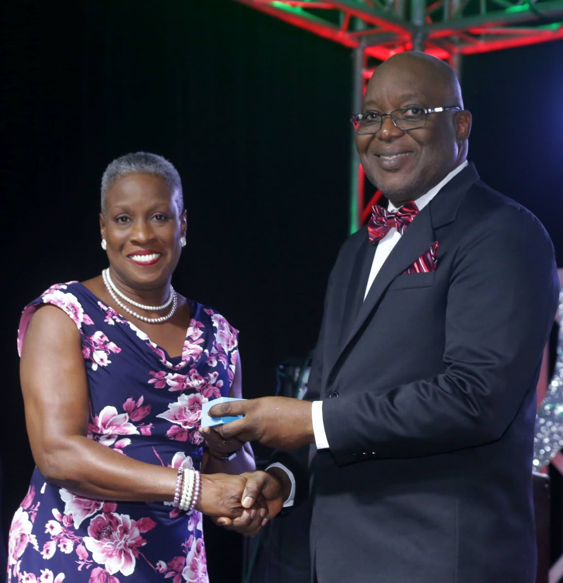 On behalf of Gywneth Armstrong, who received the Tobago Medal of Honour (Gold) for distinguished and outstanding service to Tobago in the sphere of Music, niece Merna Edwards receives the award from Chief Secretary Kelvin Charles at Tuesday night's Tobago Day Awards ceremony hosted by the Tobago House of Assembly at the Auditorium of the Shaw Park Cultural Complex.