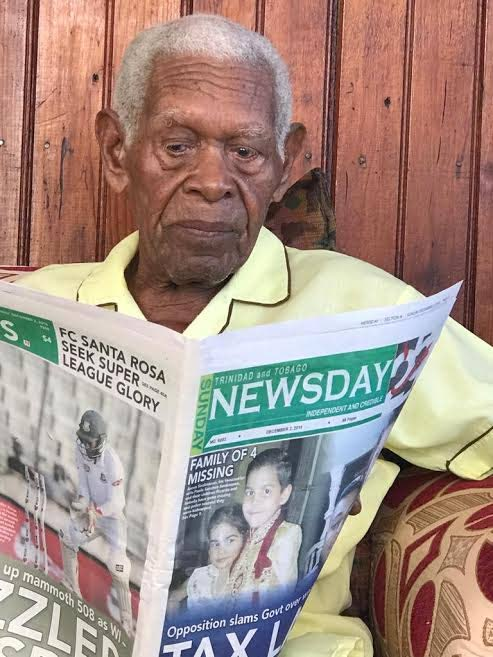 Cameron Hawkesworth, who turned 100 on November 17, reads a copy of the Sunday Newsday. He is an avid reader of the Newsday papers.