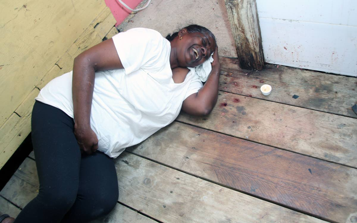 "GRIEF: Jean Subaran lies on the floor where her son Neil ""Jacko"" Bhagaloo was shot dead by gunmen at their Claxton Bay home on Thursday night."