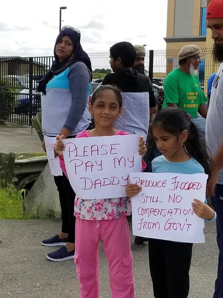 PAY DADDy: Children  of rice farmers  with placards during a November 28 protest in front of the Ministry  of Agriculture, Lands and Fisheries offices in Endeavour,  Chaguanas.