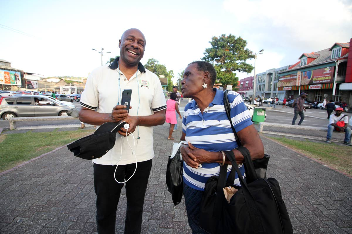 Social activist Errol Fabien listens to a woman who stopped to give him words of encouragement during his 20-hour vigil in support of Petrotrin and Caroni workers at the Cipriani statute, Cipriani roundabout, Port of Spain on Friday. He ended his vigil yesterday. PHOTO BY ROGER JACOB