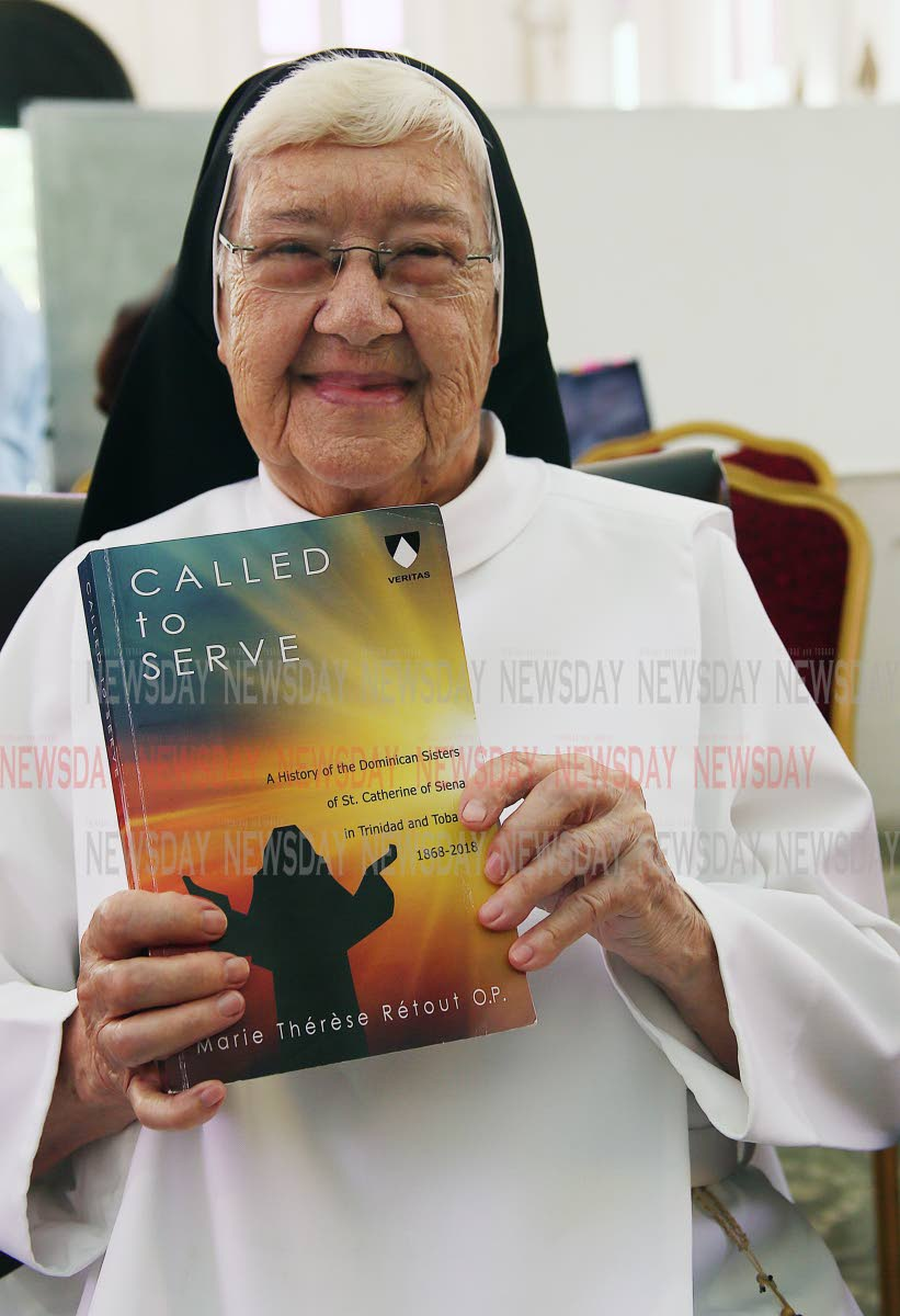 Sr Marie Thérèse Rétout OP with a copy of her book Called to Serve which tells the story of the Dominican Sisters of St Catherine of Siena in TT. PHOTO BY AZLAN MOHAMMED