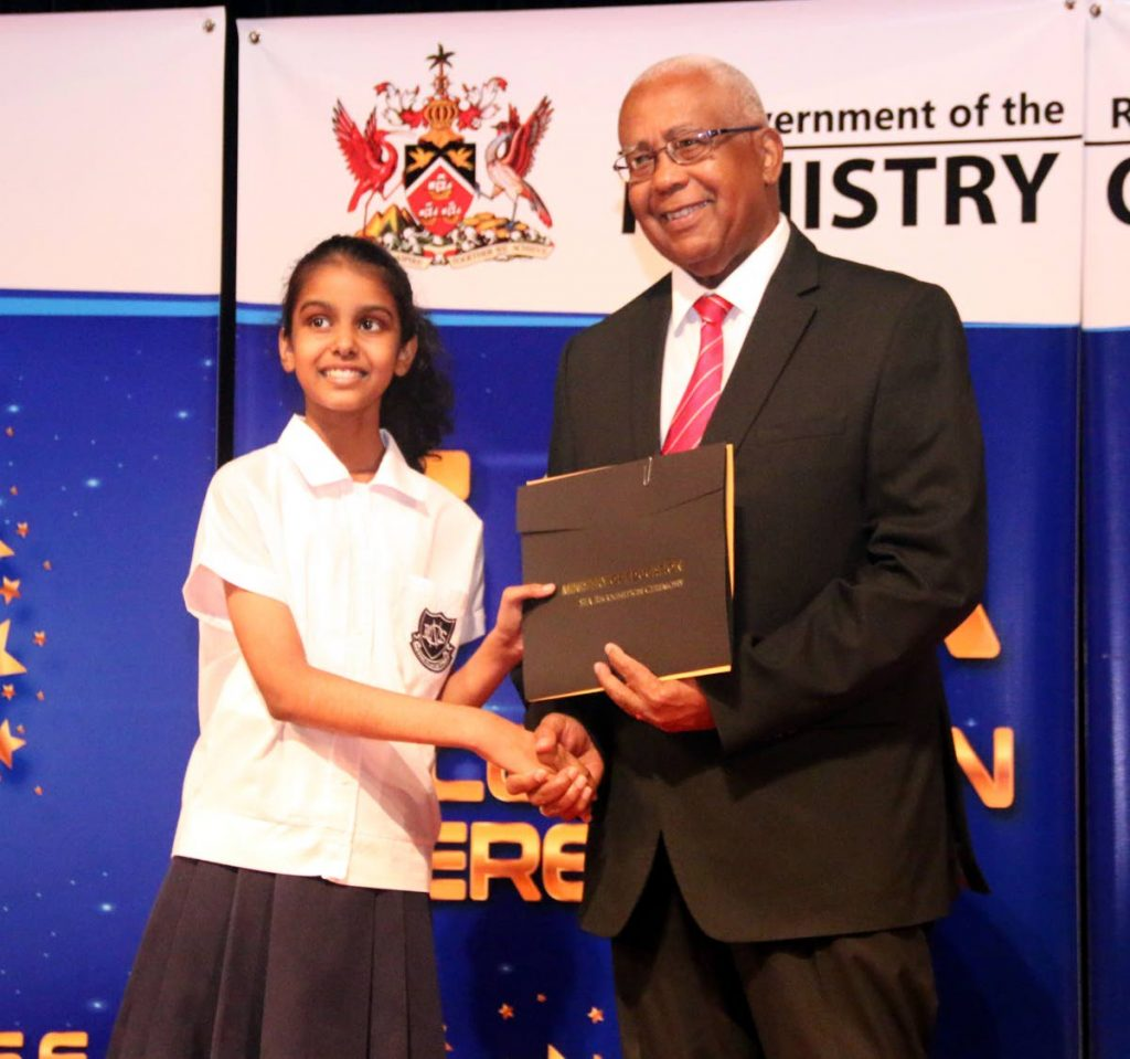 Aria Ramkhelawan of Avocat Vedic Primary School receives an award for  placing in the top 200 SEA students, from Minister of Education Anthony Garcia at SAPA on Saturday.
