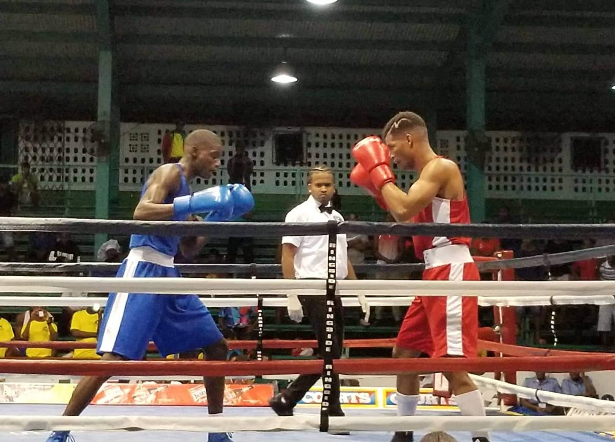 TT boxer Michael Alexander, right, puts his guard up against Guyana's Colin Lewis in a lightweight bout at the Caribbean Boxing Championships at the Cliff Anderson Sports Hall, Guyana, Friday.