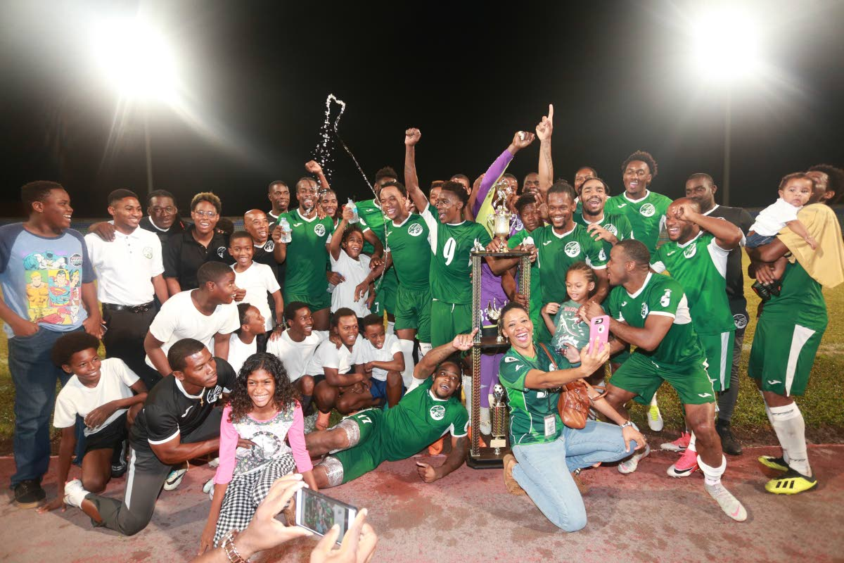 SWEET VICTORY: W Connection players, technical staff and supporters celebrate with theTT Pro League trophy after beating North East Stars 4-0 on Friday night at the Ato Boldon Stadium, Couva. PHOTO BY Allan V Crane/CA-images