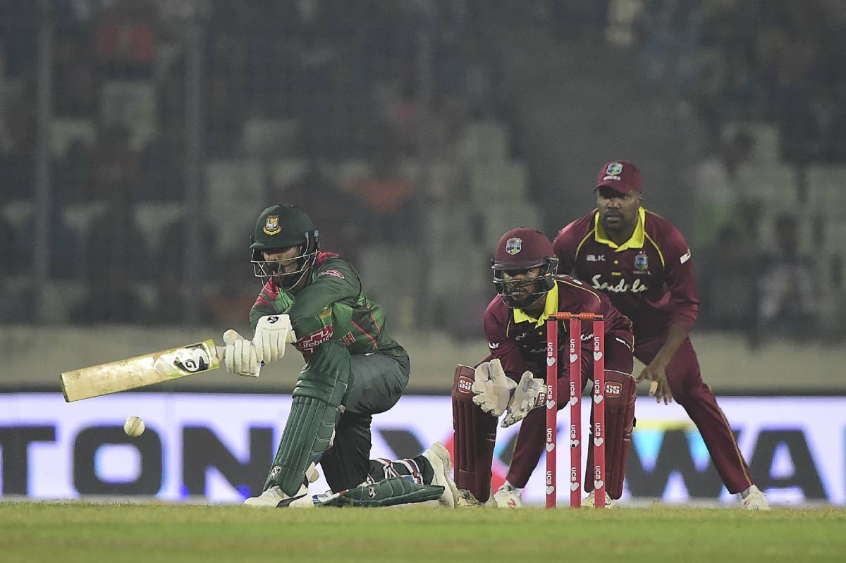 Bangladesh cricketer Liton Das (L) plays a shot as the West Indies cricketer Shai Hope (C) and Darren Bravo (R) looks on during the first One Day International (ODI) between Bangladesh and West Indies at the Sher-e-Bangla National Cricket Stadium in Dhaka on December 9, 2018. (Photo by MUNIR UZ ZAMAN / AFP)