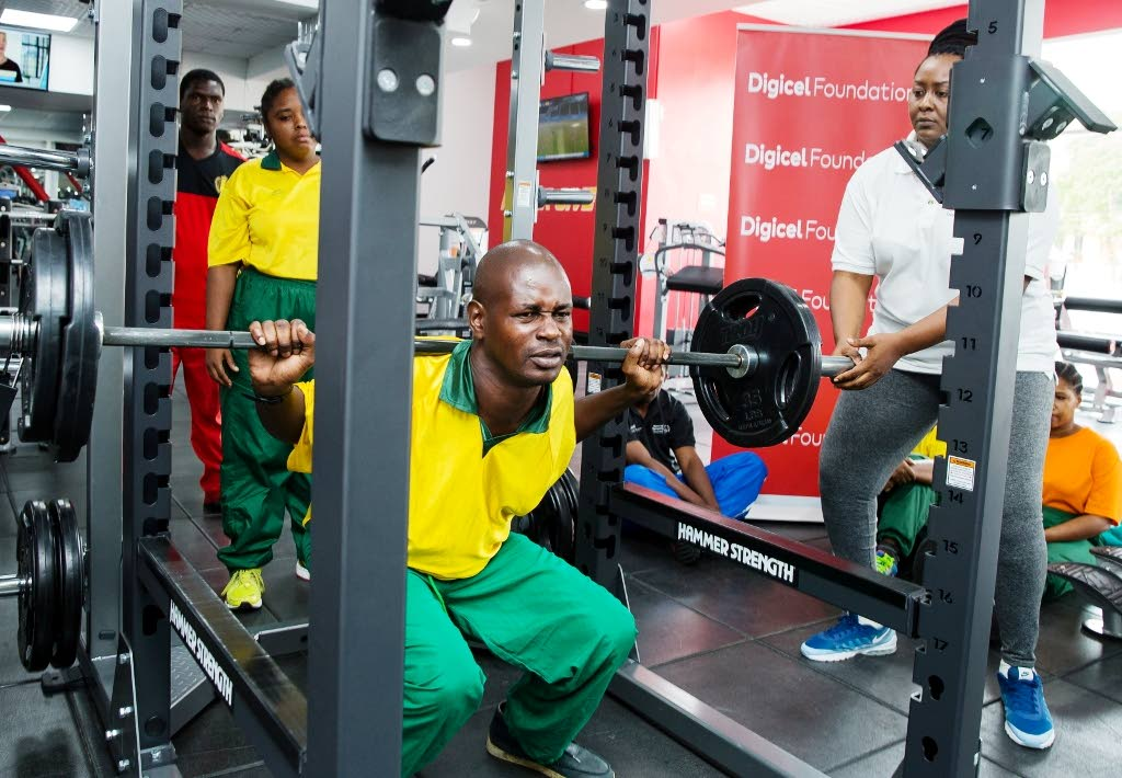Special Olympics of TT (SOTT) powerlifter  Cuthbert Joseph concentrates as he squats with the barbell on his back while other teammates look on at D' Dial Fitness Club, Long Circular Mall, St James.