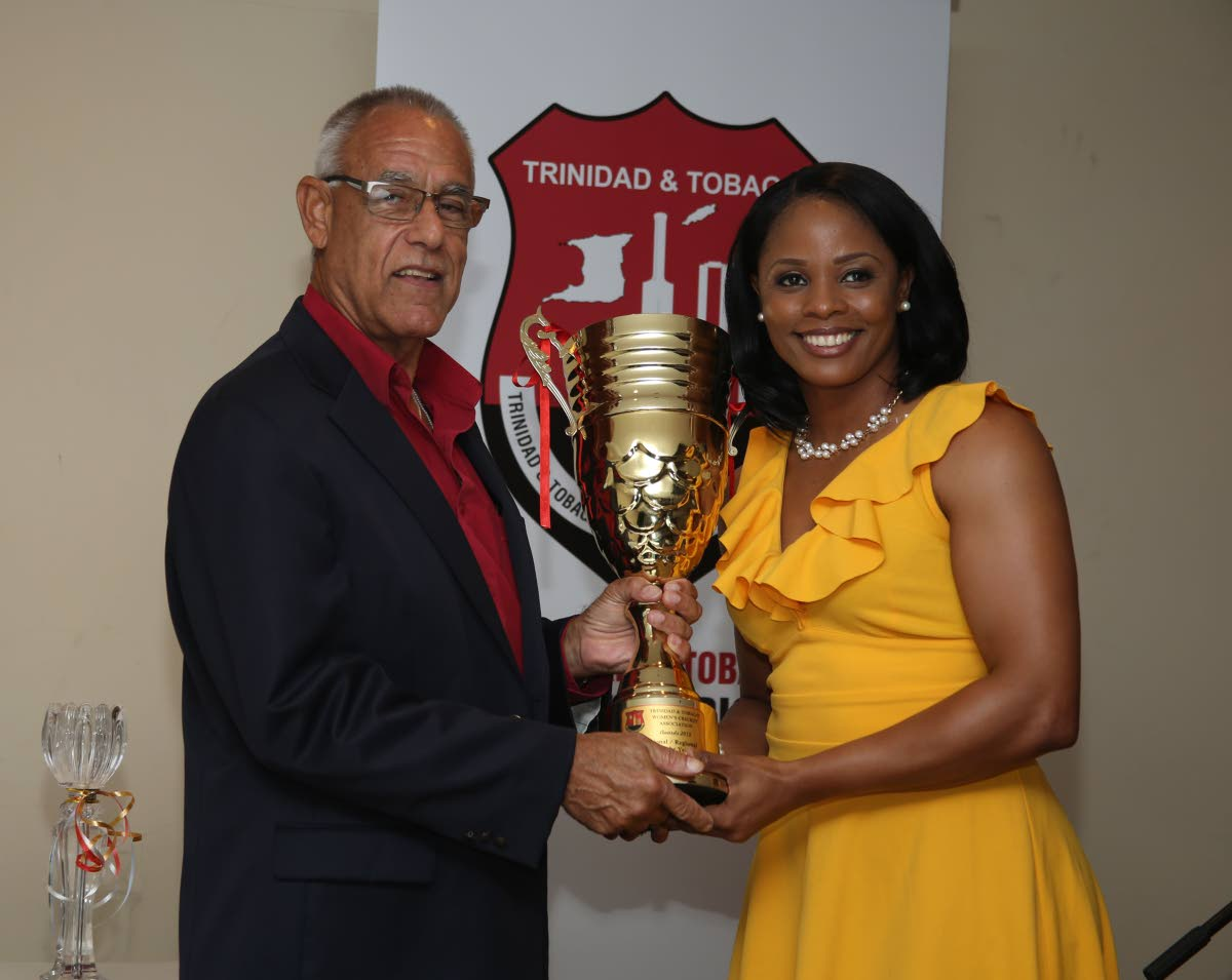 Douglas Camacho, left, Chairman of Sport Company, presents national captain Merissa Aguilleira with the national and regional Player of the Year awards at the TT Women's Cricket Association awards on Sunday at Touch and Taste Restaurant, California.