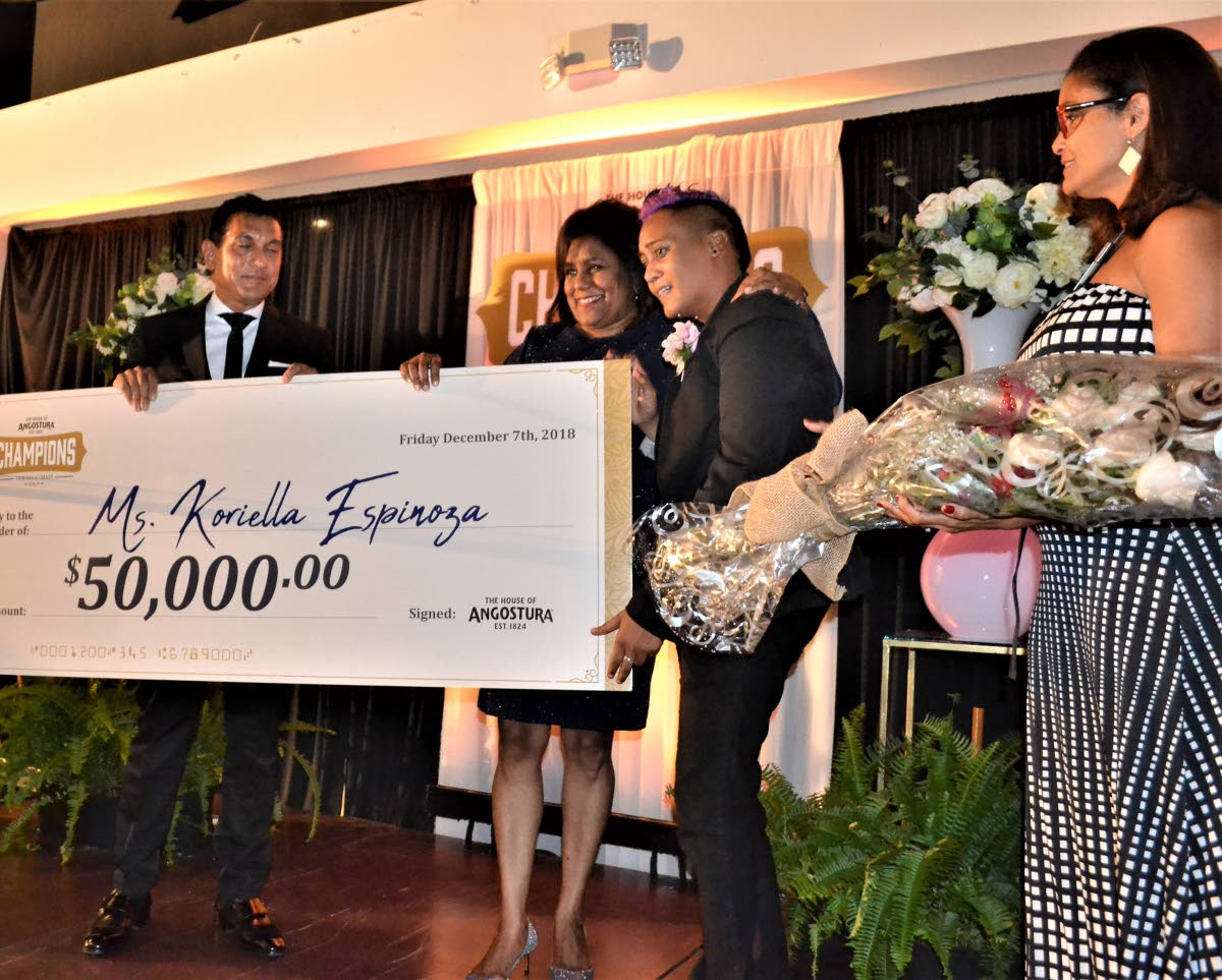 Angostura chairman Terrence Bharath and Minister of Trade Paula Gopee-Scoon present Koriella Espinoza with her cheque as Giselle La Ronde West waits to present her with a bouquet of flowers.