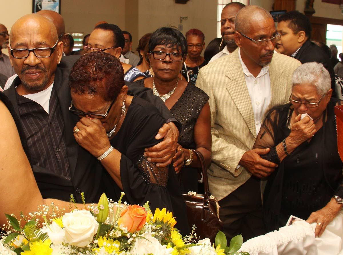 A TIME TO MOURN: Relatives of local music business icon Cleve Calderon including his wife Josephine, 2nd from left, and mother Phyllis, right, at his funeral yesterday at the Santa Rose RC Church in Arima.