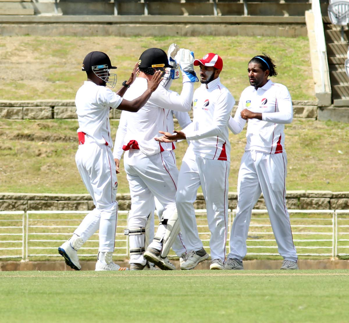 Red Force captain Imran Khan, right, celebrates one of his seven wickets with his teammates on day one of their clash with Windward Islands yesterday at Brian Lara Academy, Tarouba.
