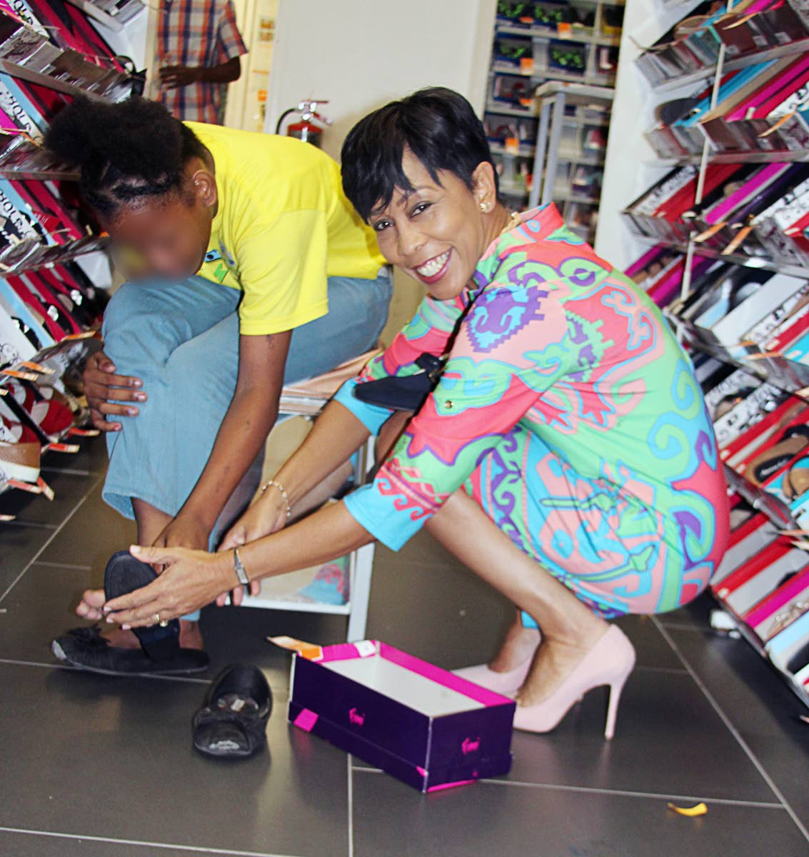 PERFECT FIT: Sharon Rowley helps this child from the Cyril Ross Nursery select a pair of shoes at Payless Shoe Store in Westmall yesterday