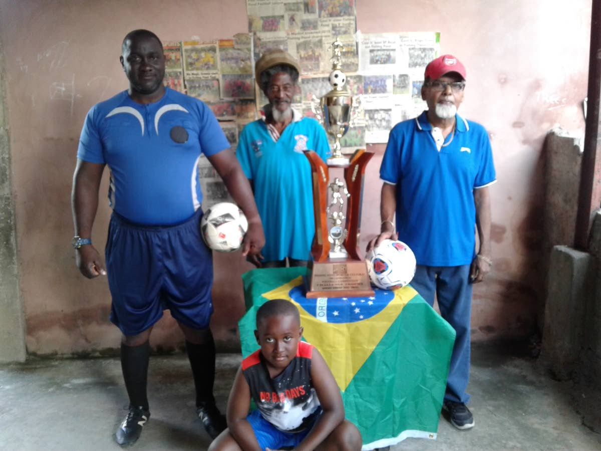 Fishing Pond Football League organiser Prakash Ramkissoon, right, with referees Shawn Brewster, left, and Andrew Joseph, as well as a young supporter.