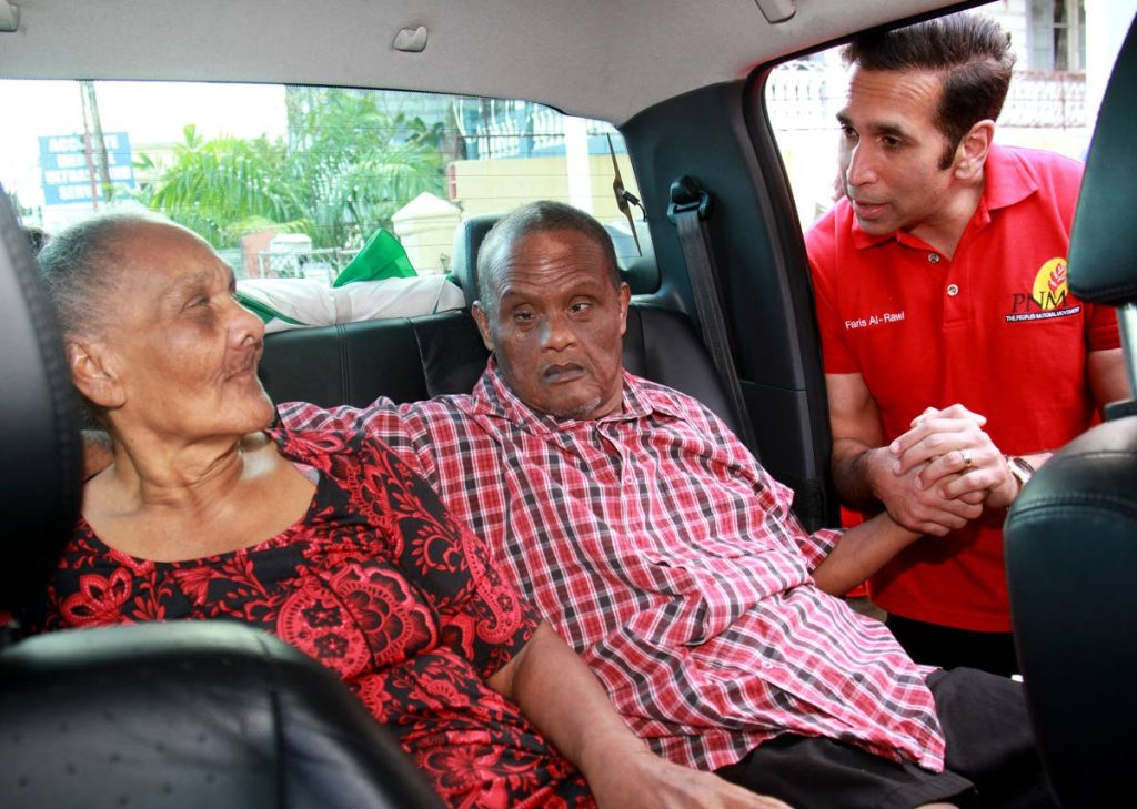 Attorney General Faris Al-Rawi greets Claude Weekes and Norma Villafana, residents of the St Vincent de Paul Home for the Aged, after he donated two wheelchairs to them at his San Fernando West constituency office on Independence Avenue yesterday. PHOTO BY ANIL RAMPERSAD.