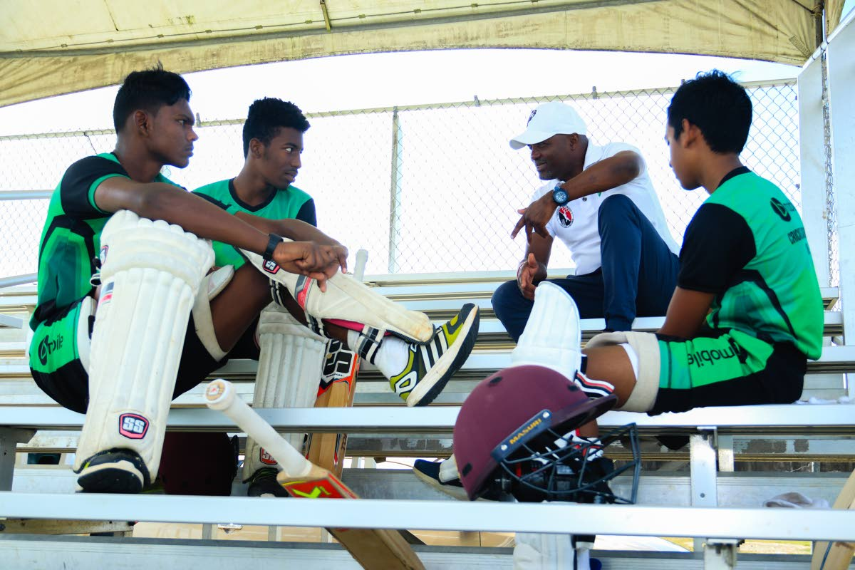 Youngsters of the bMobile Cricket Academy keenly listen to the advice of cricket legend Brian Lara, on December 8, at the  National Cricket Centre, Couva.