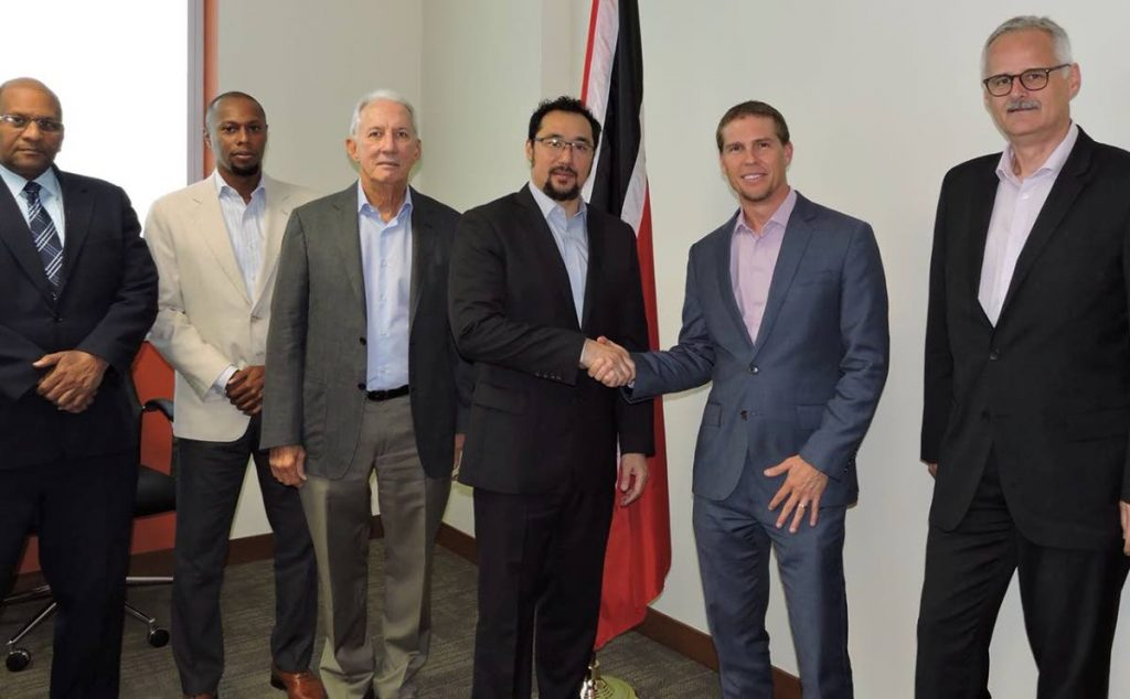 Communications Minister Stuart Young, fourth from left, shakes hands with SRI deputy chairman Adam Stewart at a meeting to discuss the Sandals Tobago project.  Third from left is Petrotrin's Chairman Wilfred Espinet.