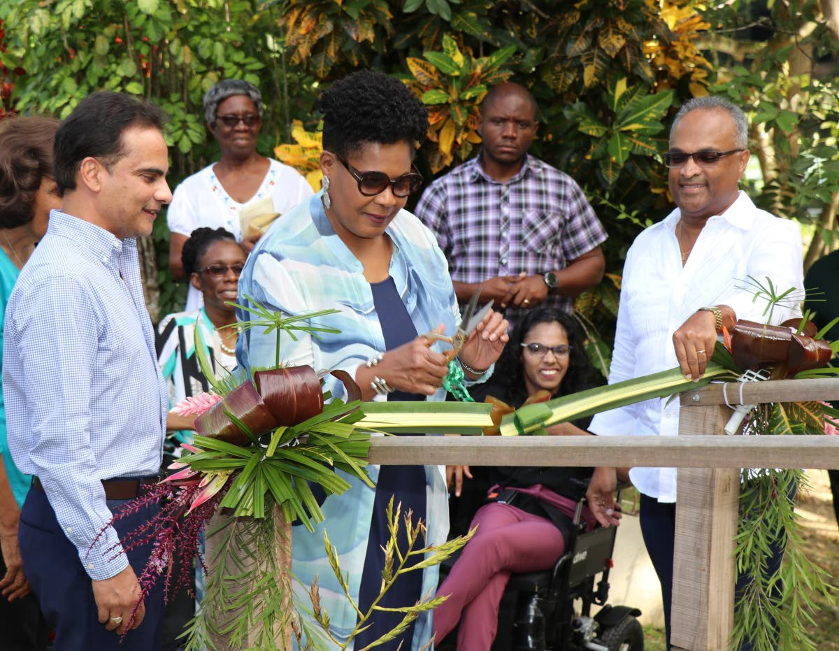 President Paula-Mae Weekes  opens the boardwalk by cutting an organic gathering of fruits and plants found at the Pointe-a-Pierre Wild Fowl Trust. Looking on are Dr Sterling Frost,  Robert Green and Shamla Maharaj.