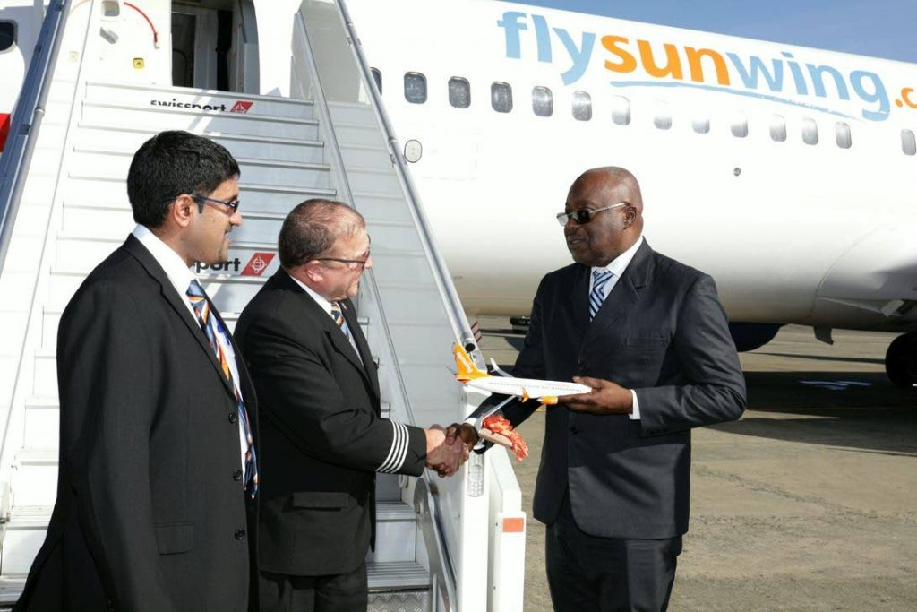 Chief Secretary Kelvin Charles, right, receives a miniature plane from pilots of Sunwing Airlines flight WG175, Marty Neel and Blair Pritchard, at the ANR Robinson International Airport last Thursday. (TTAL Photo)