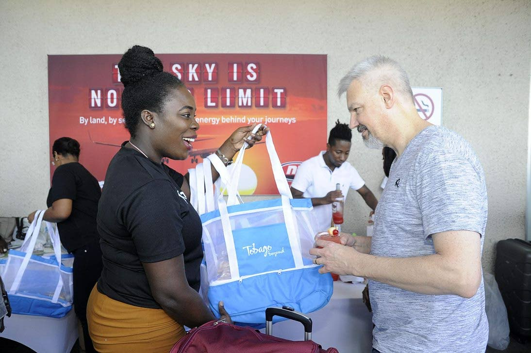 "Tobago Tourism Agency Limited's Marketing Officer Andra Joefield presents a passenger from Sunwing Airlines inaugural Toronto to Tobago flight with a ""Tobago Beyond"" beach bag filled with local sweets."