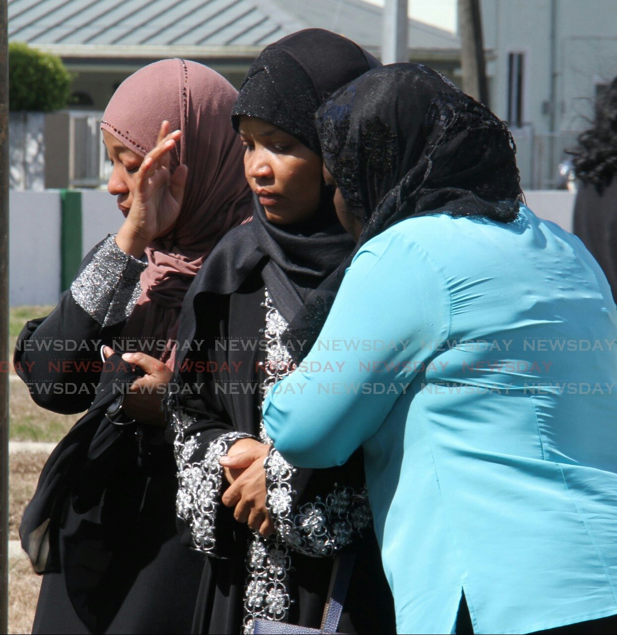 (Centre) Chimene Pantin, mother of Joash Pantin, is comforted by mourners gathered at the burial site, as the final dua prayer was being performed after laying the coffin of Joash Pantin at Monroe Road Muslim Cemetery.  Photo: Roger Jacob