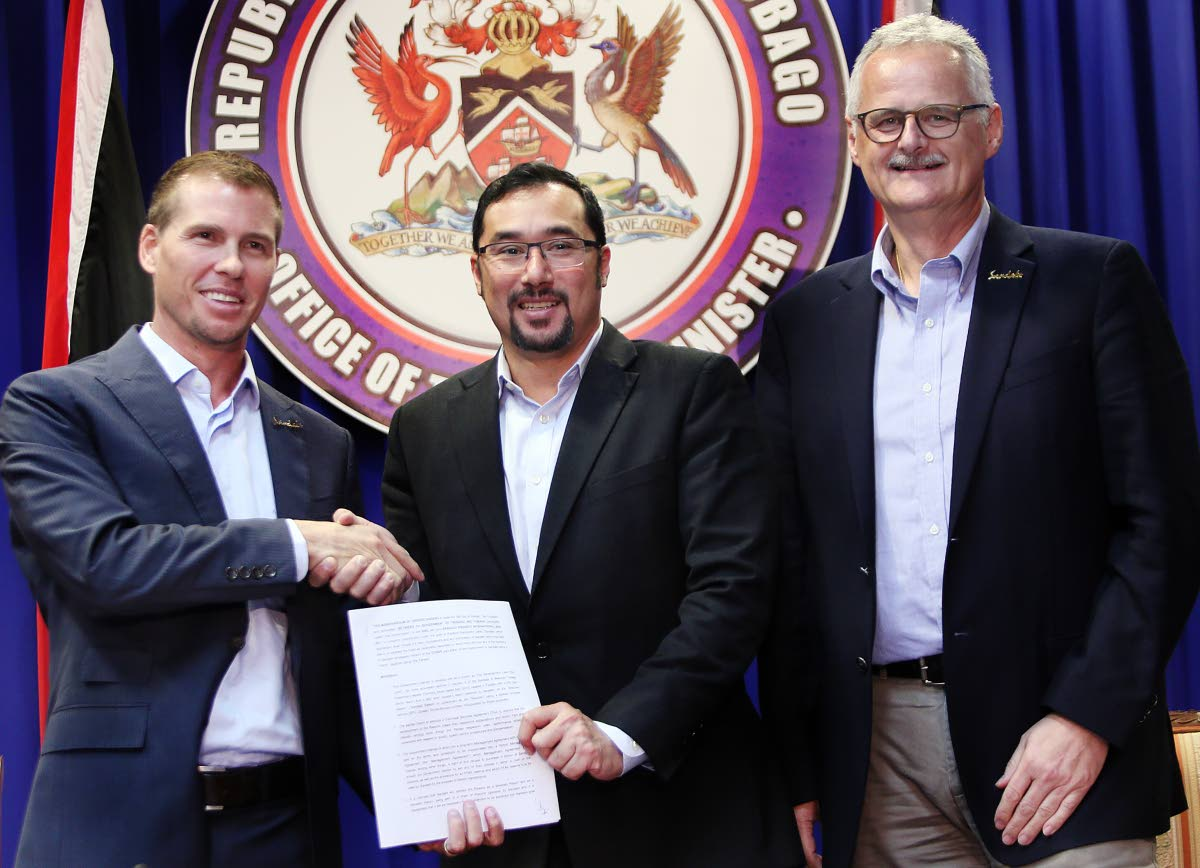 In this November 2018 file photo, Sandals group deputy chairman Adam Stewart and Minister of Communications Stuart Young  hold a copy of the MoU between the Government and Sandals for the construction of a resort in Tobago. Looking on is Sandals CEO Gebhard Rainer.