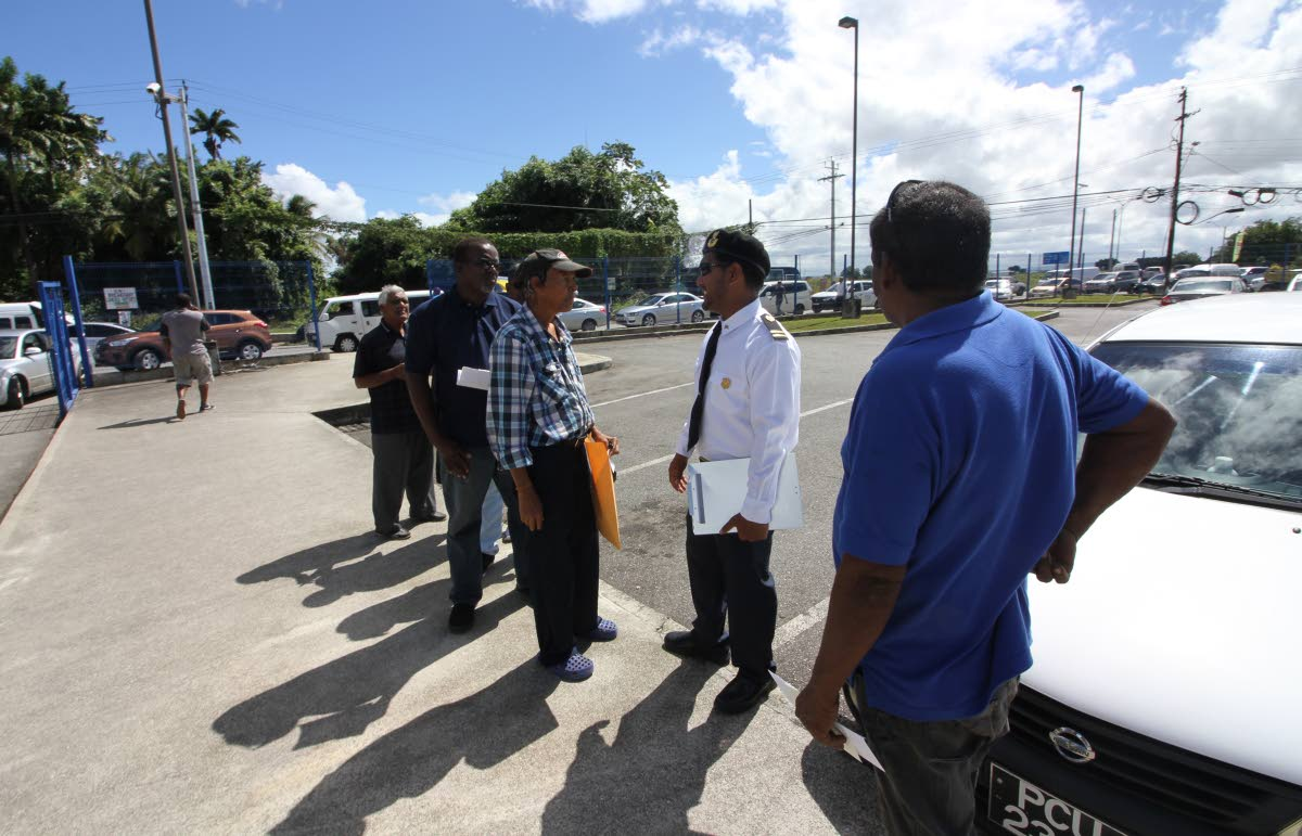 File photo: A Licensing Officer speaks with drivers waiting on their inspection certificate stickers at the Licensing Office in Caroni.