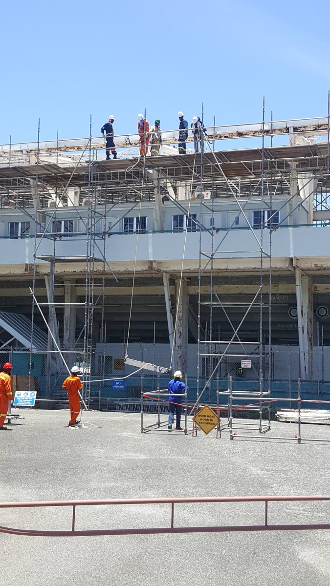 Workers work on removing the roof of the Dwight Yorke Stadium in Bacolet in August 2018 during a first phase of renovation works.