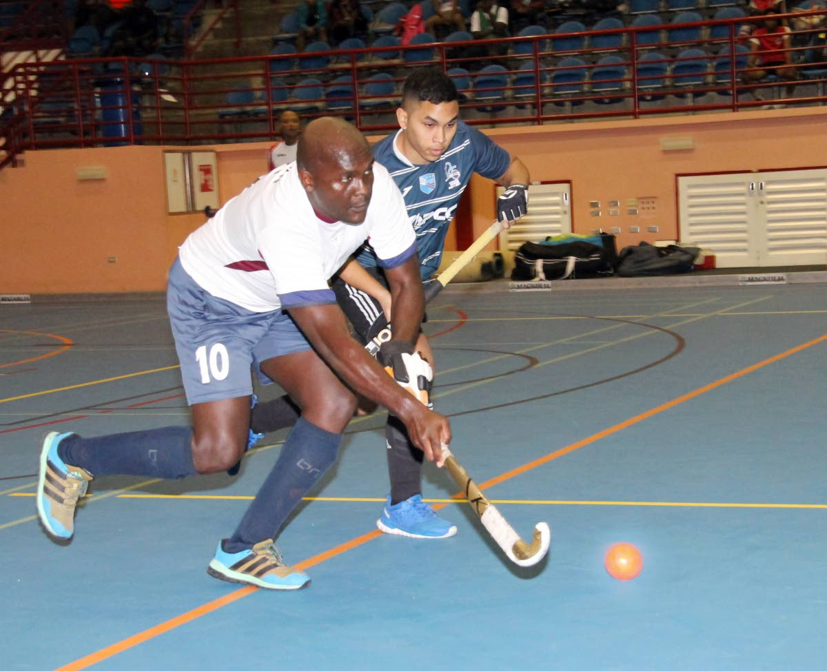 TT Defence Force's Nicholas Wren dribbles the ball as he is tracked by his Queen Park rival in the Ventures Indoor Hockey Tournament at UWI-SPEC, Friday.