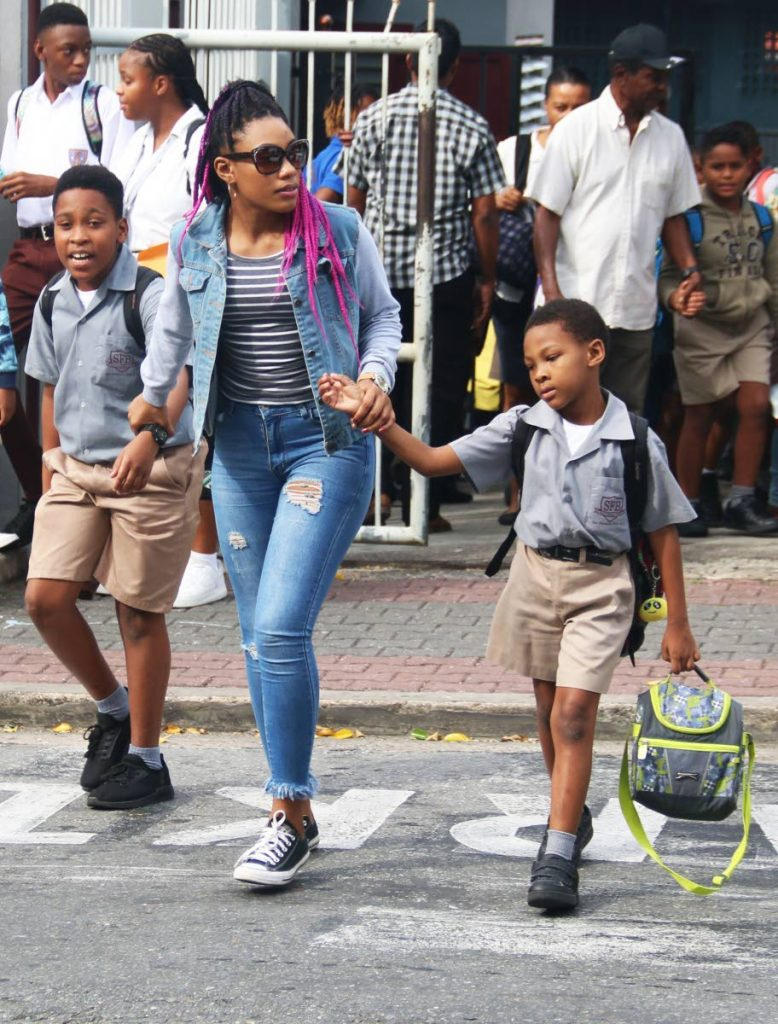 This woman assists these youngsters in crossing the road at the end of the first day of the new school term yesterday at San Fernando Boys RC School. Photo by Ansel Jebodh