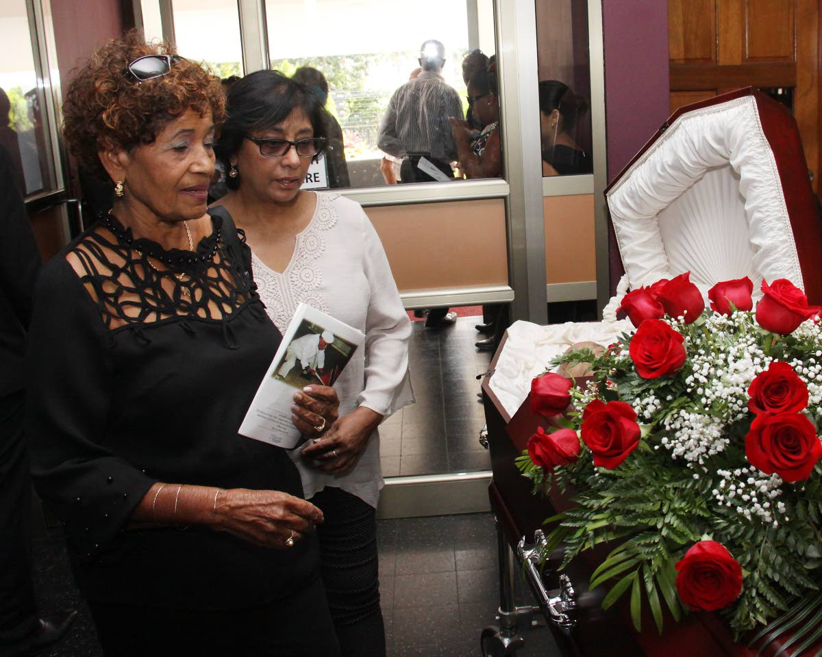 Farida Sanchez, left, looks at the body of her deceased companion Oliver Camps, at his funeral at St Finbar's RC Church, Diego Martin, yesterday. PHOTO BY ANGELO MARCELLE