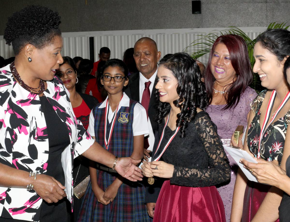 President Paula-Mae Weekes, left, speaks to Sadhana Balladin, recipient of the President's Gold Medal for High Learning, third from right, alongside other recipients; Jada Ramnath and Amrita Singh, at the President's Award ceremony honoring students' outstanding achievements in CAPE, CSEC and SEA in 2018 at the Northern Academy for the Performing Arts yesterday. PHOTO BY ROGER JACOB.