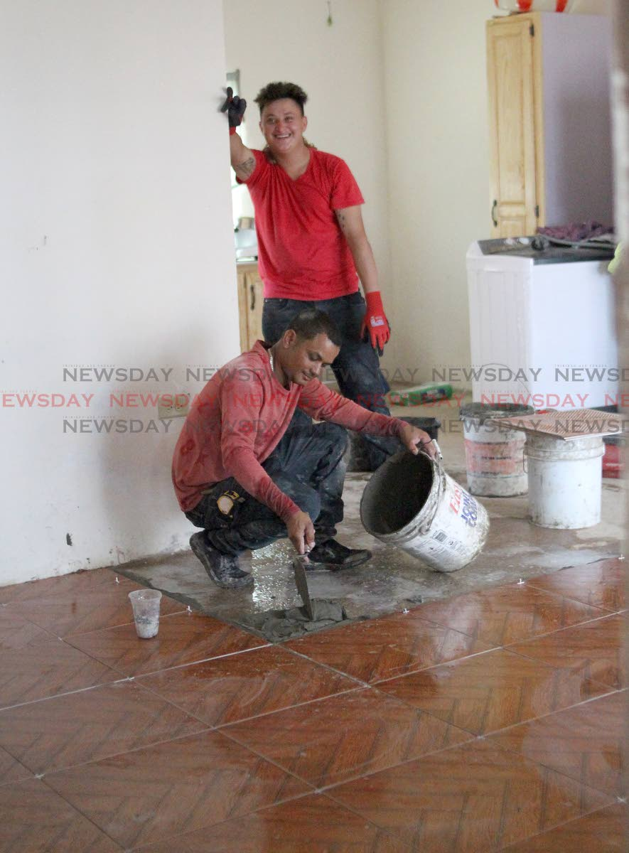 A work crew completes tile works in one of the Greenvale homes affected by devastating floods in October last year during an official tour of the area by HDC managing director Brent Lyons, and other technical staff on Thursday. PHOTO BY ROGER JACOB.