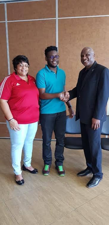 Valdano Tobias, secretary of Deaf Basketball Association TT, shakes hands with Glyne Clarke, president of Caribbean Basketball Confederation, with newly-elected president of the National Basketball Federation of TT (NBFTT) looking on.