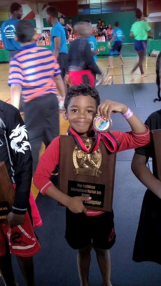Chedon Grant shows a medal and a plaque he won during the Pan American Martial Arts Tournament in Marabella last year.