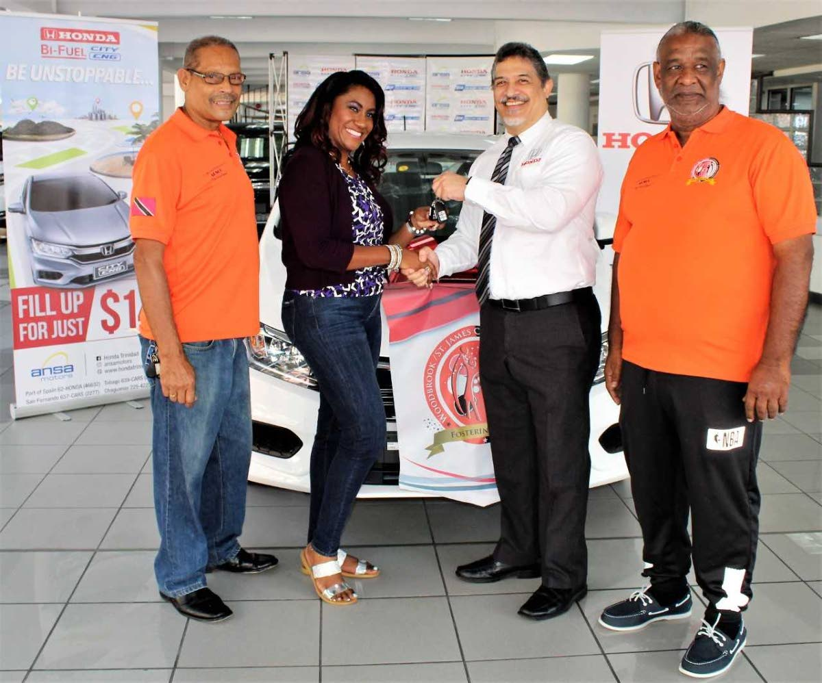 Shivaune Carter-Tam recieves her car keys from general manager  Daryl Young as Wayne Ragnauth, left, and Cleavland Garcia of the Woodbrook St James Association looks on.