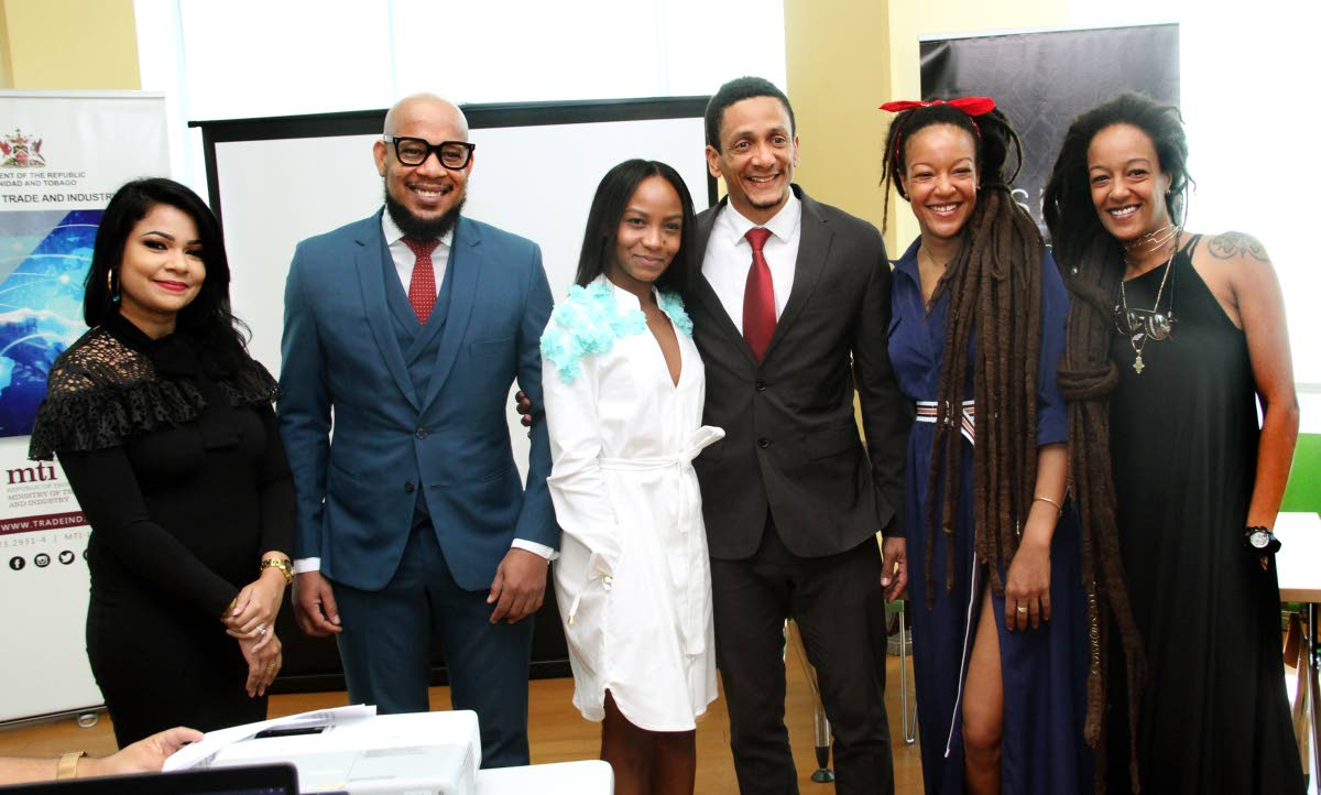 FashionTT GM Lisa Marie Daniel, designers Ecliff Elie and Jin Forde, FashionTT Chairman Jason Lindsay and twin designers Asha and Ayanna Diaz pose for a photograph at the Fashion TT press conference.