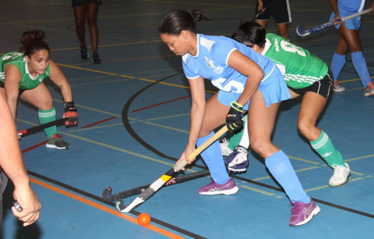 UWI's Keidi Braithwaite, centre, is tackled by Ventures' Rose-Anne Reyes, right, in the UWI Invitational Indoor Hockey Tournament on Thursday evening at UWI-SPEC, St Augustine. PHOTO BY ANGELO MARCELLE