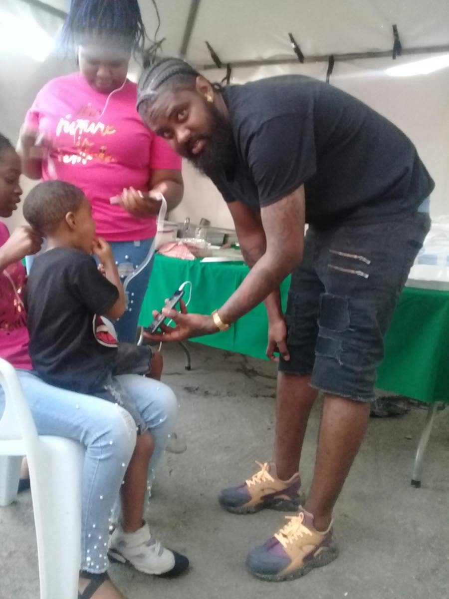 Barber Kendell Paul shares a light moment with his son  Kerdell during Tin Man's New Image Barbershop's recent customer appreciation day in Sangre Grande.