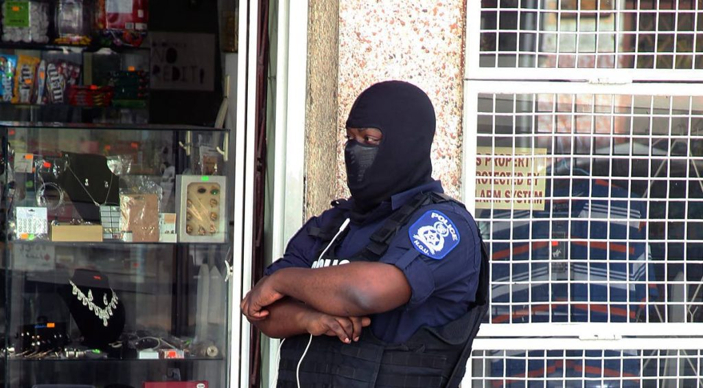 Despite a financial squeeze on the Police Service with Government only releasing funds to pay salaries, officers continue to do their duty including this one who stood guard yesterday near the Port of Spain Magistrates Court while high-risk prisoners were being escorted to the courthouse.