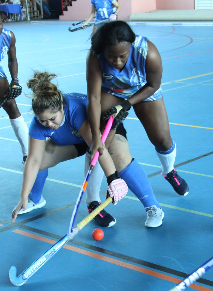 UWI's Blair Obrien,left, receives a strong challenge from Antonia Gordon of Police, during their match up in the, UWI 2nd Invitational Indoor Hockey tournament, at UWISPEC, St. Augustine, yesterday.  Photo: Angello Marcelle