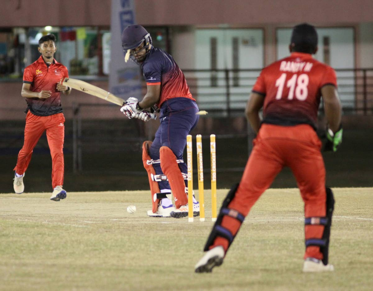 BOWLED: Combined Campuses and College's Leonardo Friginette looks back at his wicket as he is bowled by TSATT's Amit Sankar (L), on Saturday night, during their UWI World Universities T20 match, at the Sir Frank Worrell Ground, St Augustine.