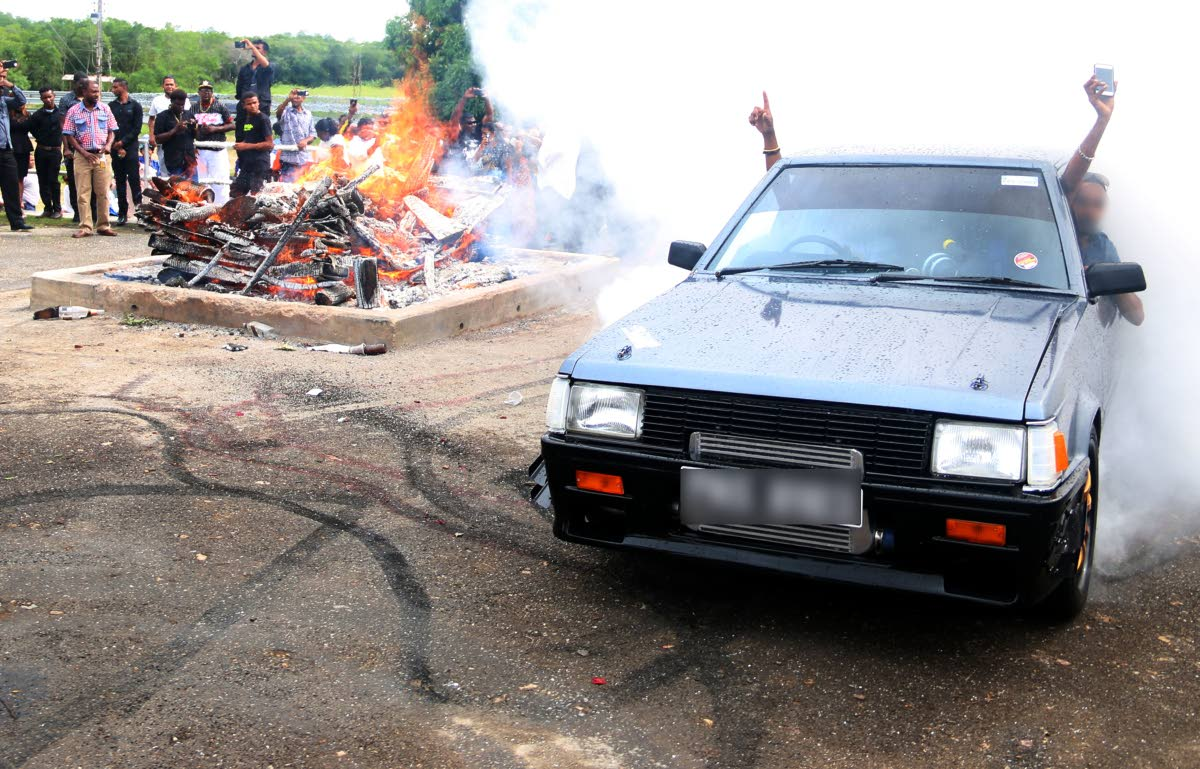 NO RESPECT: Men perform stunts in a car near a burning funeral pyre last week at the Shore of Peace cremation site in Mosquite Creek. FILE PHOTO