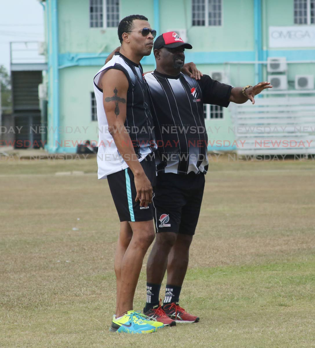 HELPING HAND: Former West Indies pacer and new Red Force assistant coach Mervyn Dillon, left, observes a training session alongside head coach Kelvin Williams, right, at the National Cricket Centre, Couva, yesterday. PHOTO BY VASHTI SINGH
