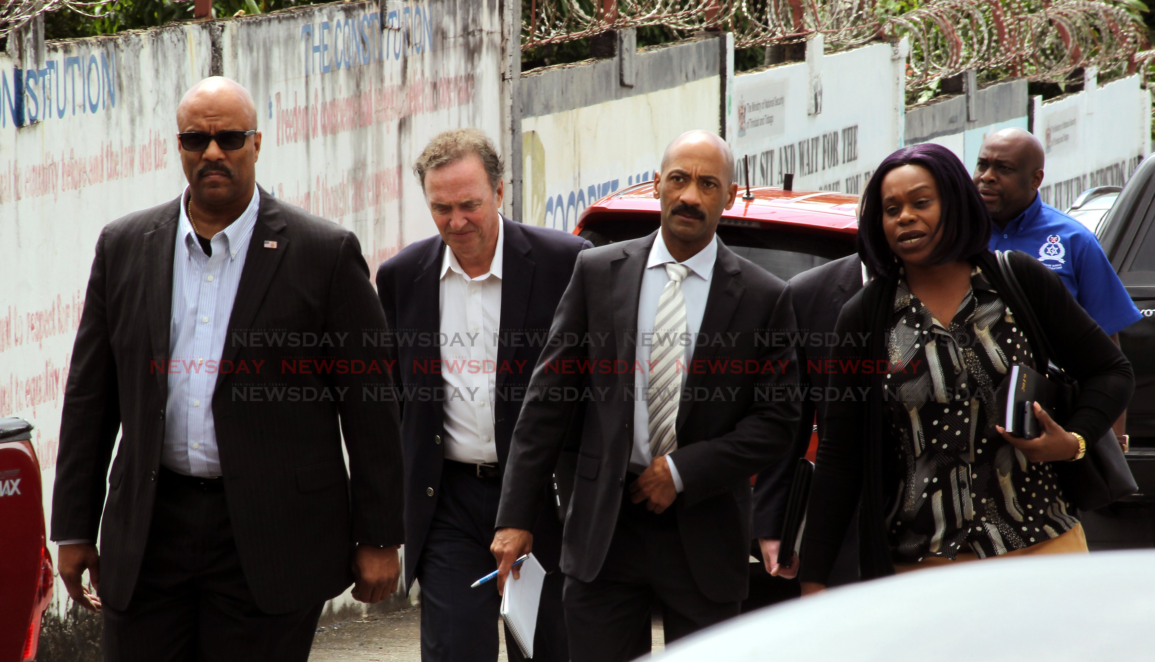 (at right) A female police officer leads a delegation of foreign nations to the murder scene of the latest homicide where Kias James was shot dead, Lady Hochoy Road, Cocorite.  Photo: Roger Jacob