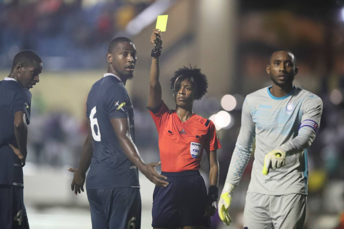 In this July 25,2017 file photo, match referee Crystal Sobers issues Police FC's Jibri Mc David (#6) a yellow card and a penalty to North East Stars, during the TT Pro League match between North East Stars and Police FC, at the Arima Velodrome. North East Stars won 3-2.